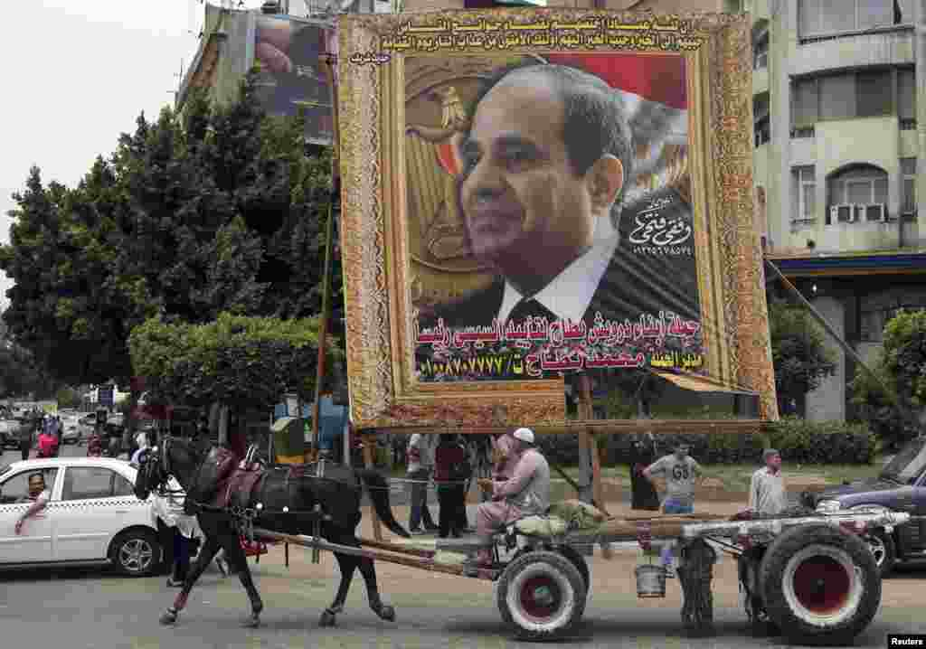 A man on a horse cart rides past a huge banner of former army chief Abdel Fattah al-Sissi, in downtown Cairo, May 6, 2014.