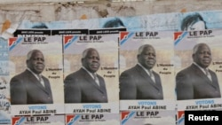 FILE - Election posters for opposition candidate Ayah Paul Abine of the People Action Party are pasted on a wall in the capital Yaounde, Cameroon, Oct. 7, 2011.