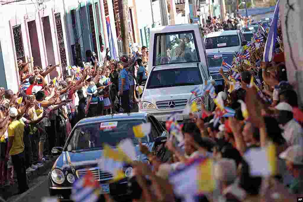 Đức Giáo Hoàng Benedicto đi trên xe dành riêng cho giáo hoàng trong khi dân chúng tụ tập dọc theo đường đi để chào đón ngài khi đến Santiago de Cuba ngày 26 tháng 3, 2012. (Hình AP/ Osservatore Romano)