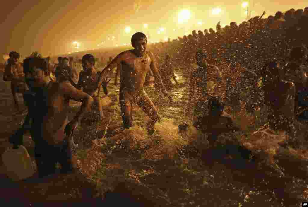Seorang pria India melompat di air sungai Sangam, anak sungai Ganga pada festival Mandi Agung di Allahabad, India (14/1).
