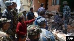 27일 네팔 카트만두의 지진으로 무너진 건물에서 구조요원들이 생존자 수색 작업을 벌이고 있다.