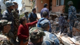 Nepalese resident Sangita Mahat, center, directs police as they retrieve the body of her relative Prasamsah, 14, during rescue efforts in Balaju in Kathmandu, April 27, 2015.