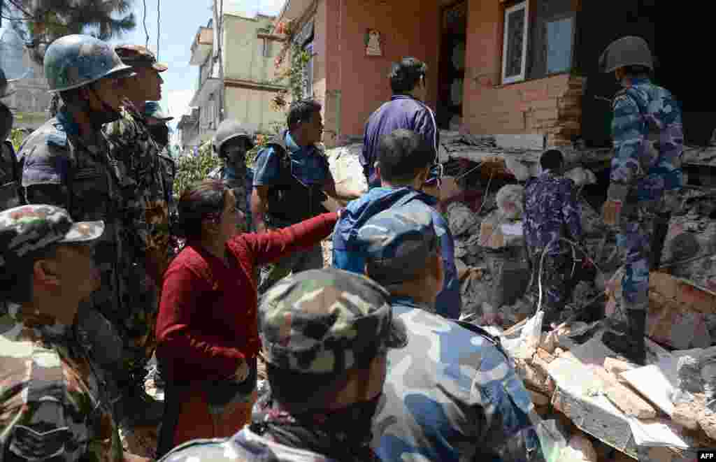 Nepalese resident Sangita Mahat, center, directs police to retrieve the body of her relative during rescue efforts in Balaju in Kathmandu.