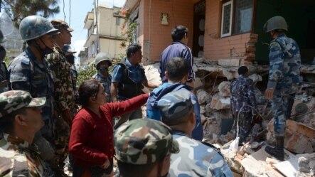 Cư dân chỉ địa điểm nơi thân nhân của bà bị chôn vùi cho lực lượng cứu hộ tại Balaju, Kathmandu, ngày 27/4/2015.