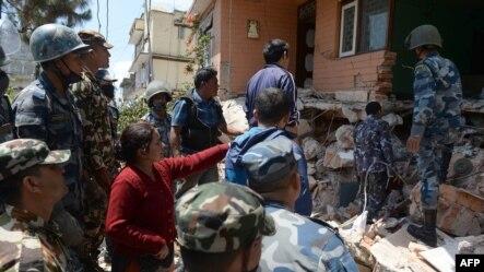 Nepalese resident Sangita Mahat, center, directs police as they retrieve the body of her relative Prasamsah, 14, in Balaju in Kathmandu, April 27, 2015.
