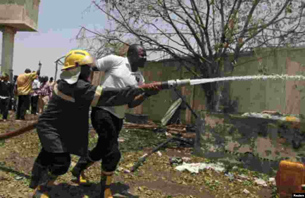 Firefighters drag a hose through the damaged building of Nigerian newspaper This Day after a bomb blast in its premises in Abuja April 26, 2012.