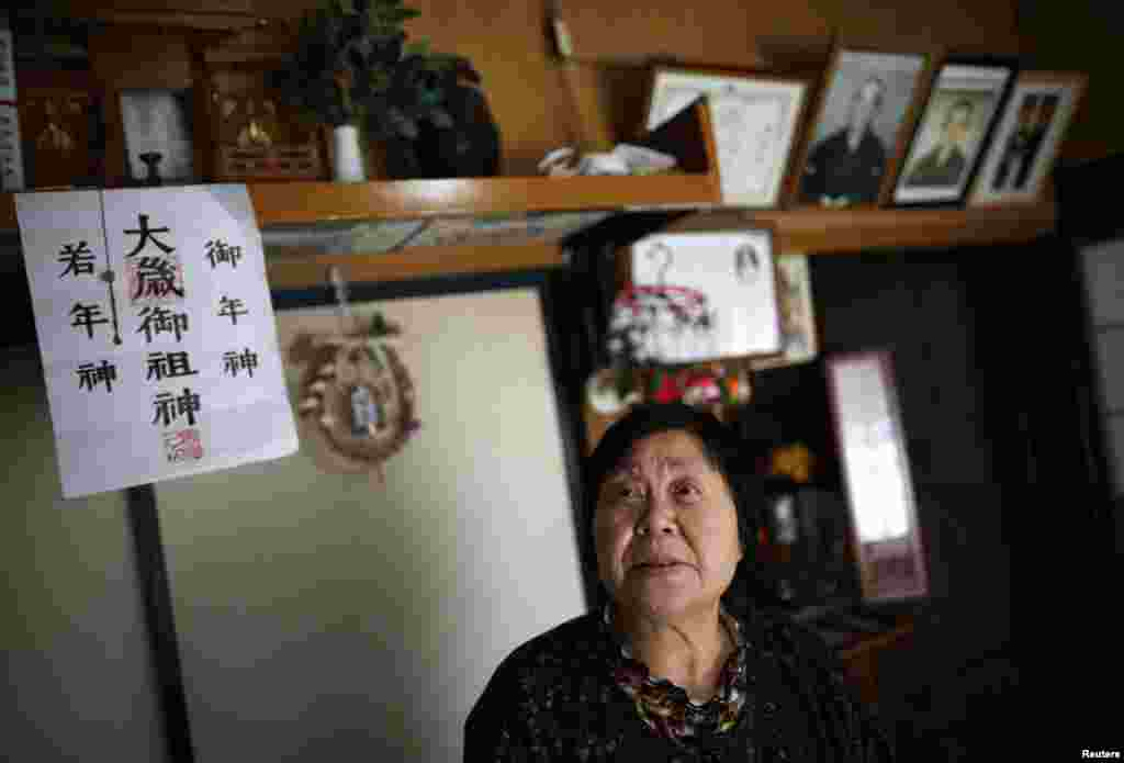 Kimiko Koyama, who evacuated from Miyakoji three years ago, looks up inside her house with portraits of her deceased parents in the background, Tamura, Fukushima prefecture, April 1, 2014.