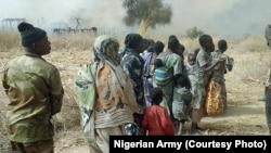FILE - Nigerian soldiers rescue some people after chasing Boko Haram fighters out of a village in the Sambisa forest in Borno state, in 2016.