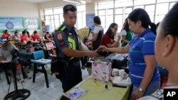 필리핀 마닐라의 투표소에서 경찰관이 13일 투표를 하고 있다.