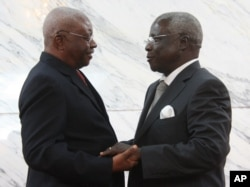 FILE - Mozambique President Arnando Guebuza, left, and former Renamo rebel leader Afonso Dhlakama, right, shake hands after signing a peace accord, Sept. 5, 2014.