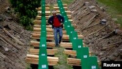 Čovek traži kovčeg sa posmrtnim ostacima svog rođaka pred sahranu novoidentifikovanih žrtava u Potočarima