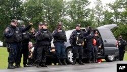 Cảnh sát vẫy chào người đi đường hoan hô họ sau khi David Sweat bị bắt giữ, ngày 28 tháng 6, 2015, ở thị trấn Constable, New York.