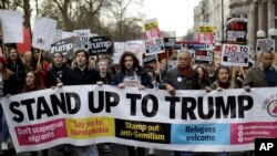 People hold a banner as they take part in a protest march in London, against U.S. President Donald Trump's ban on travelers and immigrants from seven predominantly Muslim countries entering the U.S., Feb. 4, 2017.