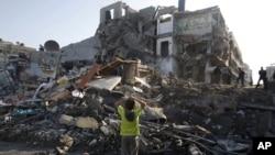 Trẻ em Palestine đứng trong đống đổ nát sau cuộc tấn công của Israel nhắm vào một ngôi nhà ở thành phố Gaza, ngày 20/11/2012.
