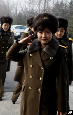 Members of the Moranbong Band and the State Merited Chorus of North Korea walk to get on a train at the station in Pyongyang, North Korea, Wednesday, Dec. 9, 2015.
