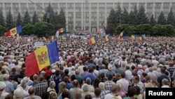 "Protesters carry Moldova's national flags during an anti-government rally, organised by the civic platform ""Dignity and Truth"" (DA), in central Chisinau, Moldova, Sept. 6, 2015."