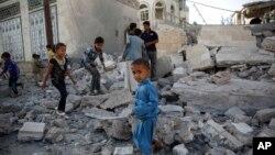 Trẻ em chơi đùa giữa những đống đổ nát của một ngôi nhà bị phá hủy vì 1 cuộc không kích do Ả Rập Xê-út lãnh đạo, ở Sana'a, Yemen, 8/9/2015.