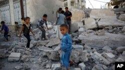 지난해 9월 예멘 사나에 사우디 연합군의 공습이 있은 후 무너진 건물 터 위에서 아이들이 놀고 있다. (자료사진)