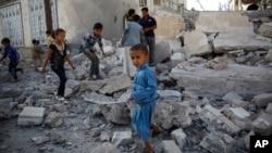 也门儿童在首都萨那一处空袭后的废墟上玩耍(资料图)