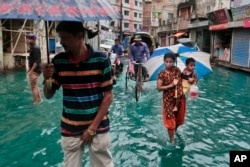Bangladeshi people walk through a waterlogged street after heavy rainfall in Dhaka, Bangladesh, Saturday, May 21, 2016.