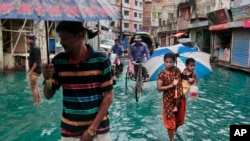 孟加拉人在达卡的积水的街道上行走(2016年5月21日)