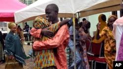 ໜຶ່ງໃນບັນດາເດັກຍິງ Chibok ທີ່ຖືກປ່ອຍຕົວ ກຳລັງກອດກັບສະມາຊິກຄອບຄົວຂອງລາວຄົນໜຶ່ງ ໃນລະຫວ່າງ ພິທິລວມຕົວກັນໃໝ່ກັບຄອບຄົວໃນນະຄອນຫຼວງ ອາບູຈາ, ໄນຈີເຣຍ. 16 ຕຸລາ, 2016.