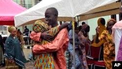 Salah satu dari siswi Chibok yang diculik dipeluk anggota keluarganya dalam reuni mereka di Abuja, Nigeria (16/10). (AP/Olamikan Gbemiga)