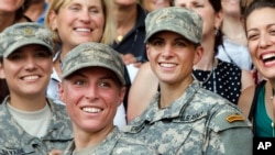 FILE - U.S. Army 1st Lt. Shaye Haver, center, and Capt. Kristen Griest, right, pose for photos with other female West Point alumni after an Army Ranger school graduation ceremony at Fort Benning, Ga., Aug. 21, 2015.
