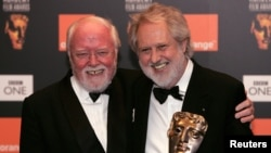 Director David Putnam (R) is embraced by fellow British Director Richard Attenborough (L) after winning the Fellowship Award at the British Academy of Film and Television Arts awards in central London in this February 19, 2006 file photo.