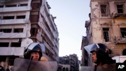 Egyptian police stand guard at the scene of a powerful explosion at a police headquarters building in the Nile Delta city of Mansoura, Egypt, Dec. 24, 2013.