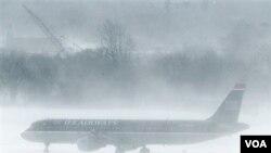 Pesawat U.S. Airways parkir di bandara Philadelphia saat terjadi badai salju lebat. Sekitar 10.000 penerbangan di Timur Laut AS dibatalkan akibat badai salju.