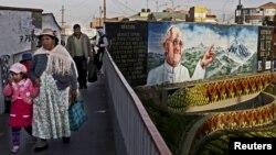 Residentes de El Alto, Bolivia, caminan frente a un mural alusivo a la visita del Papa a Ecuador, Bolivia y Paraguay.