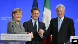 German Chancellor Angela Merkel (L), France's President Nicolas Sarkozy (C) and Italy's Prime Minister Mario Monti shake hands at the end of a news conference after a trilateral meeting on eurozone crisis in Strasbourg, eastern France, November 24, 2011