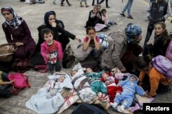 FILE - Five Syrian babies, three of them triplets, left to center, lie in blankets among their relatives as they arrive with other refugees and migrants aboard the passenger ferries Blue Star Patmos and Eleftherios Venizelos from the islands of Lesbos and Chios at the