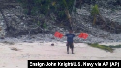 This photo provided by U.S. Navy released Thursday, April 7, 2016, shows a man waving a life jacket as a U.S. Navy P-8A maritime surveillance aircraft discovers them on the uninhabited island of Fanadik.