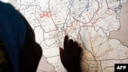 FILE - Evalina, a South Sudanese teenage victim of sexual abuse, points on a map to Unity state in South Sudan, indicating the location where she used to live, March 9, 2015. She said she escaped to Khartoum after being imprisoned by gunmen and sexually abused.