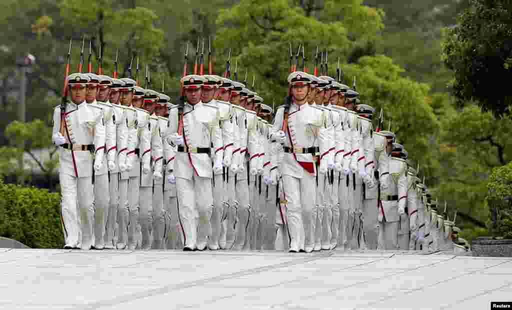 Members of Japan's Self-Defense Force's honor guard march before a ceremony for Prime Minister Shinzo Abe at the Defense Ministry in Tokyo.