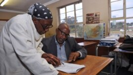 South African musician, Sipho 'Hotstix' Mabuse (R), 60, talks with a classmate as he attends class in a school in Soweto, April 25, 2012.