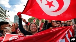 People hold Tunisian flags as they demonstrate two days after gunmen attacked the museum and killed scores of people in Tunis, Tunisia, March 20, 2015.