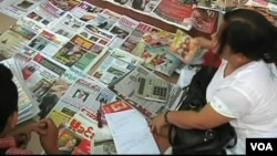 Burmese customers at a news stand.