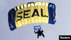 A U.S. Navy SEAL, who is a member of the Navy parachute team 'Leap Frogs', takes part in a demonstration of combat skills at the National Navy UDT-SEAL Museum in Fort Pierce, Florida, November 11, 2011.