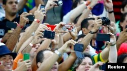 Spectators record the ongoing match between Japan and Ivory Coast with their smartphones during their 2014 World Cup Group C soccer match in Recife, Brazil, June 14, 2014.