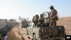 FILE - In this Dec. 22, 2015 photo, Afghan security forces patrol in Nad Ali district of Helmand province, Afghanistan. Late on Sept. 23, 2017, Taliban insurgents ambushed and killed the district police chief and his three bodyguards.