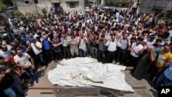 Warga Palestina melakukan shalat jenazah bagi sebuah keluarga yang tewas akibat serangan Israel di Jalur Gaza (22/7).