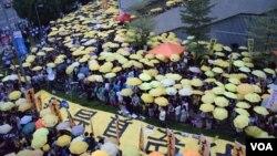 接近1,000名集會人士高舉黃傘默站,紀念香港警察去年向示威者施放催淚彈。(美國之音特約記者湯惠芸照)