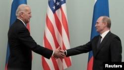 Joe Biden, alors vice-président des États-Unis (à g.), serre la main de Vladimir Poutine, alors premier ministre de la Russie, lors de leur rencontre à Moscou le 10 mars 2011. Les deux hommes sont désormais présidents de leurs pays respectifs.