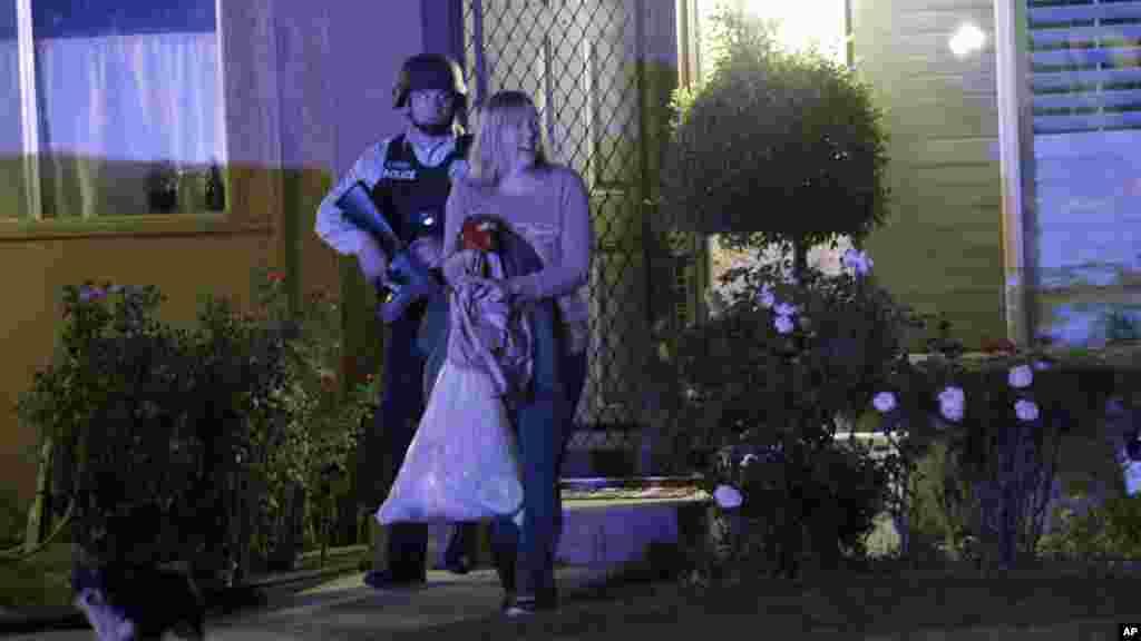 Un policier accompagne une femme chez elle après la fusillade, à Redlands, en Californie, 2 décembre 2015.,