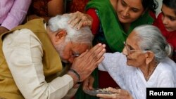 Narendra Modi (kiri), calon perdana menteri dari Partai Bharatiya Janata memohon restu dari ibunya Heeraben di rumahnya di Gandhinagar, Gujarat (16/5/2014). Modi akan menjadi Perdana Menteri India yang baru.