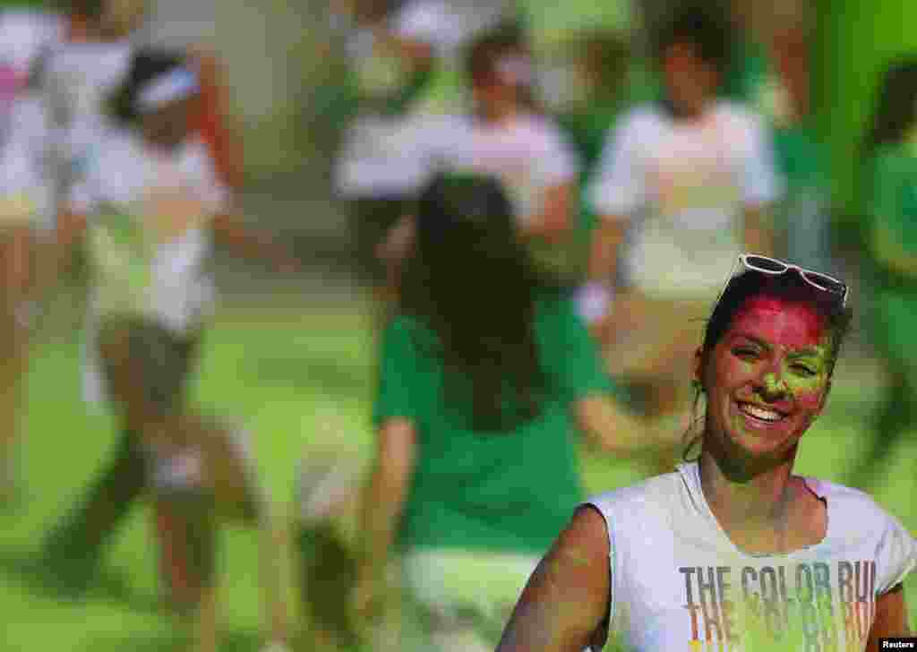 A woman smiles while taking part in The Color Run in Brussels. The Run is a five-kilometer, untimed race, held in cities worldwide, with the aim of promoting healthy living. Participants are doused from head to toe in different colors at each kilometer.