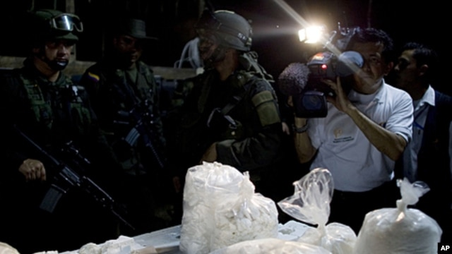 A members of the press photographs packages of seized cocaine during a drug presentation by police in Puerto Gaitan, some 150 miles southeast of Bogota, Colombia, Oct. 13, 2011.